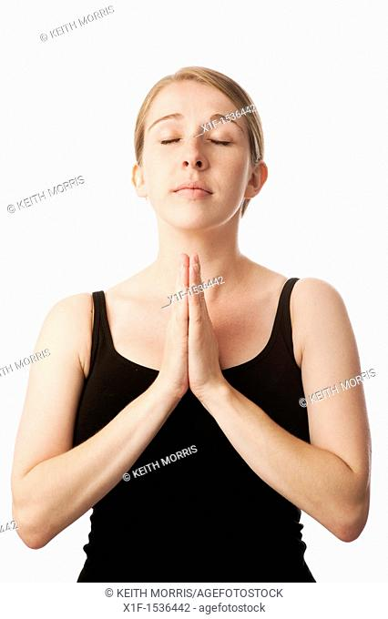 a young caucasian woman looking angelic and praying with her hands together