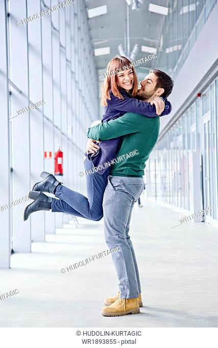 Young couple embracing in airport building