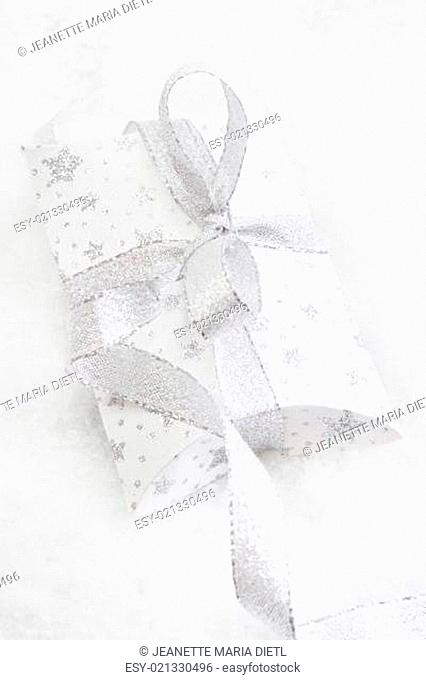 Close up of white present box with silver ribbon for christmas on white background