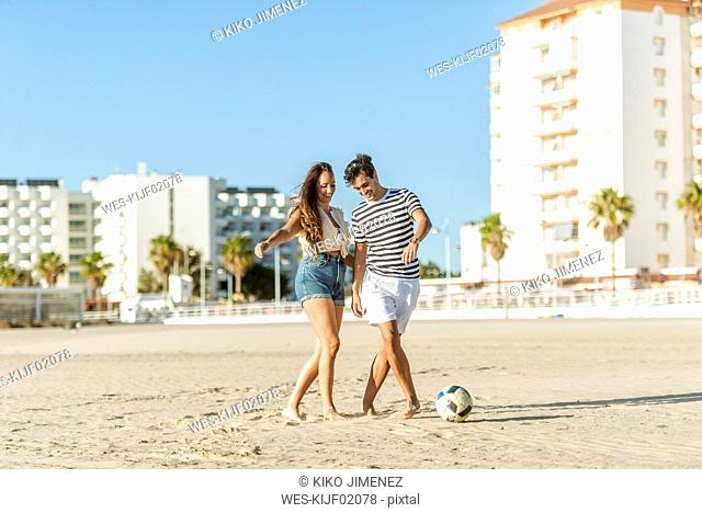 Happy young couple playing soccer on the beach