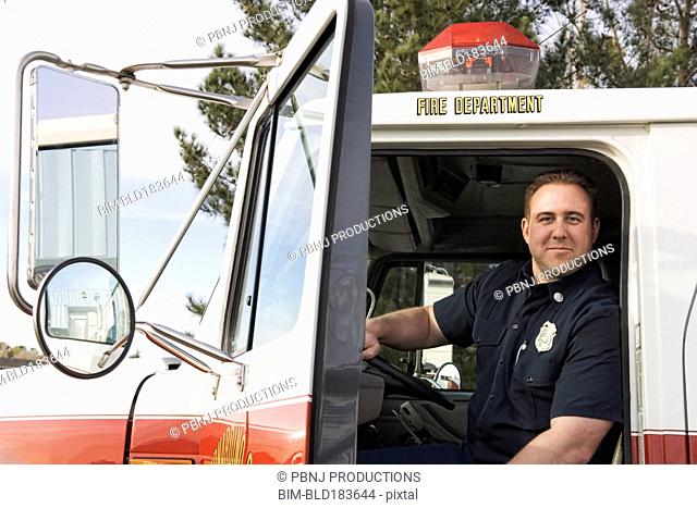 Caucasian firefighter smiling in fire truck