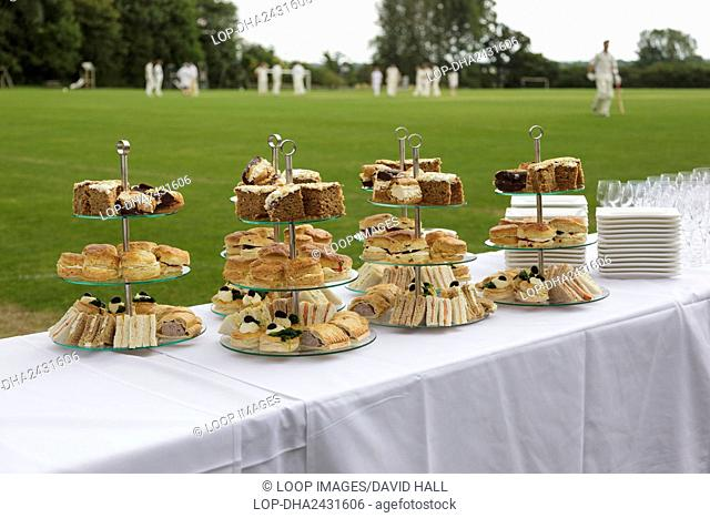 Afternoon tea laid out on tables next to a village cricket pitch