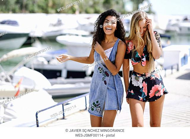 Two laughing young women at waterfront promenade in summer