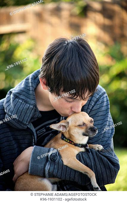 young man caring for small Chihuahua