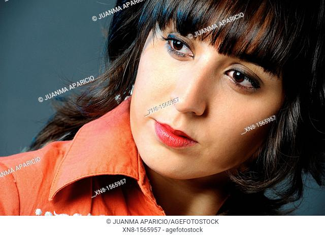 Portrait of beautiful young woman with dark hair, orange shirt and red lipstick looking sideways