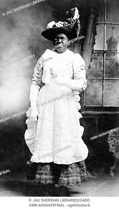 Full length standing portrait of mature African American woman, wearing light blouse, dark skirt, light apron with frills, gloves and elaborate hat