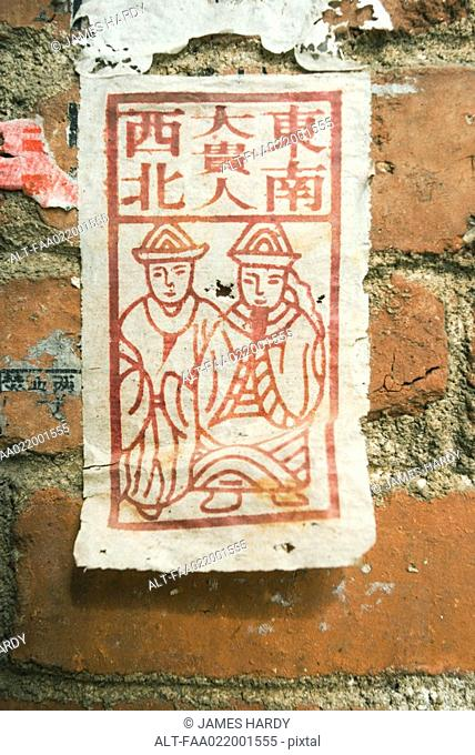 Flyer pasted to wall with Chinese script and figures