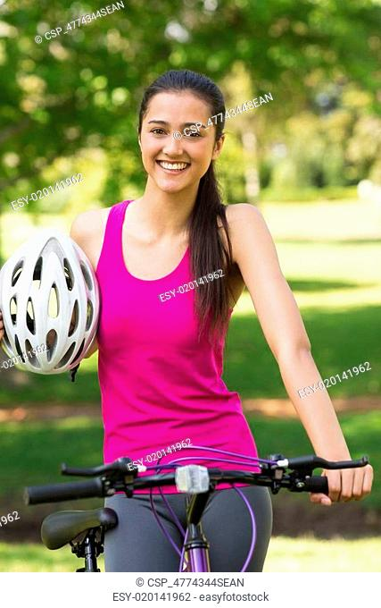 Fit woman with helmet riding bicycl