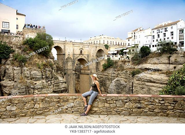 Woman Sitting on Stone Fence by Ronda`s New Bridge, Andalucia, Spain
