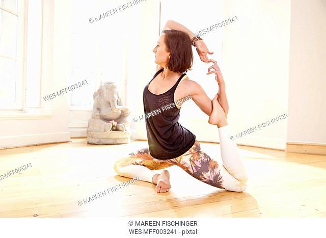 Woman in sunny yoga studio getting into Parivrrta Janu Sisasana pose