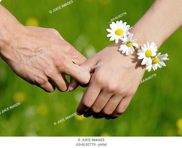Close up of couple holding hands with flower bracelet