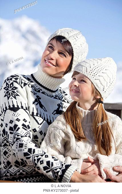 Mother and daughter on balcony at ski resort