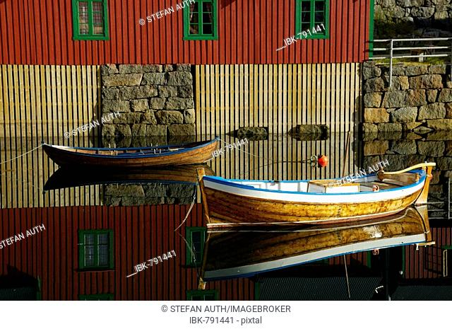 Red painted wooden house and rowboats reflected in the water, Stamsund, Vestvagoey, Lofoten, Norway, Scandinavia