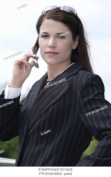 A woman looks at the camera as she holds the cell phone