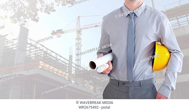 Mid section of construction man holding plan and hard hat