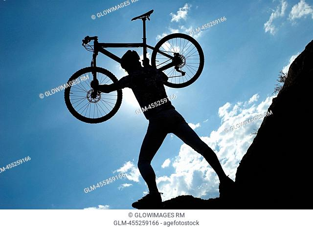 Silhouette of a man carrying a mountain bike