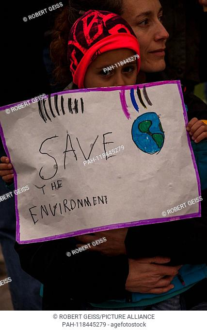 """Mother and child during rally against climate change. Writing """"""""Save the environment"""""""". 15.03.2019 