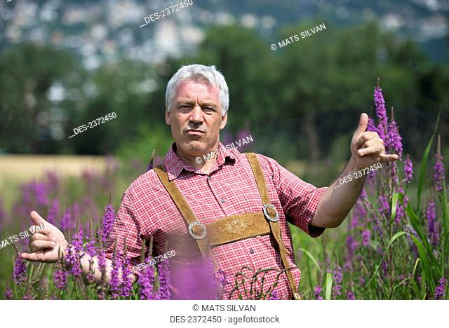 A Man Standing In A Field With Purple Blossoms Giving The Shaka Sign With His Hands; Locarno, Ticino, Switzerland