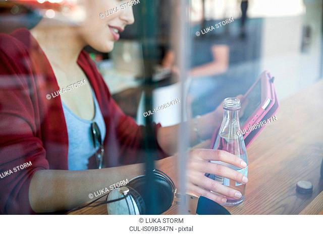 Young woman sitting in cafe, holding bottle of water, using digital tablet