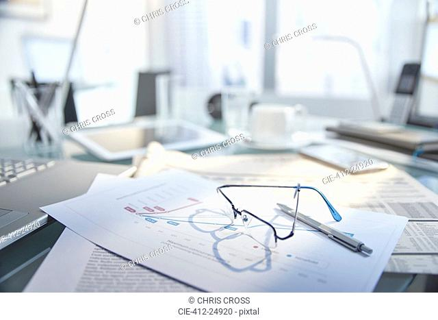 View of messy desk with glasses and pen on top of papers