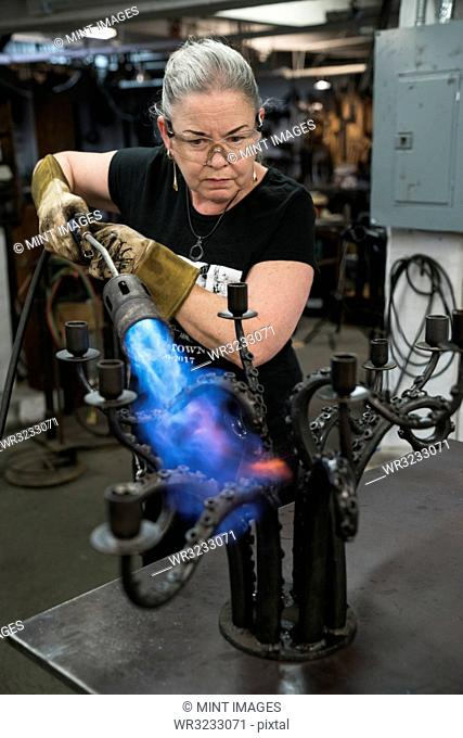 Caucasian female blacksmith using a torch to heat a metal candelabra in her studio