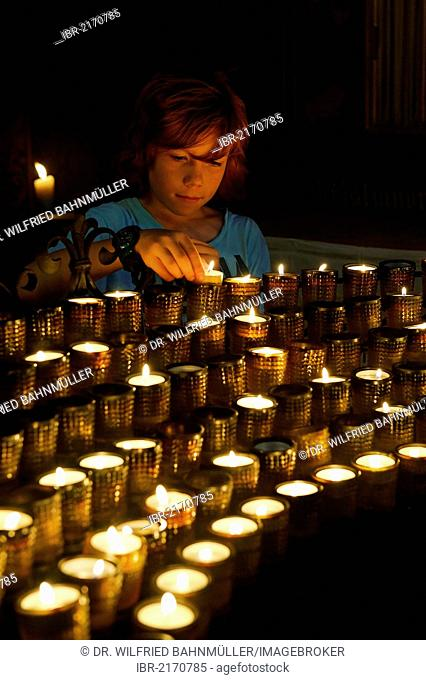 Child lighting a votive candle in a church, Cathedral of St Peter, Worms Cathedral, Worms, Rhineland-Palatinate, Germany, Europe