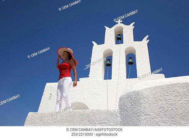 Woman in front of a church bell, Byzantine church of Agia Irini near the Ormos harbour, Ios, Cyclades Islands, Greek Islands, Greece