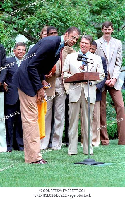 Kareem Abdul Jabbar bends over to speak in the microphone when President Reagan hosted the NBA champion Los Angeles Lakers at the White House