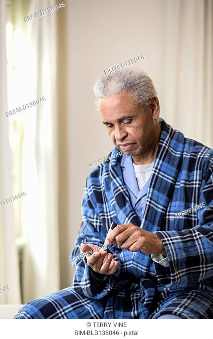 Senior African American man testing blood sugar