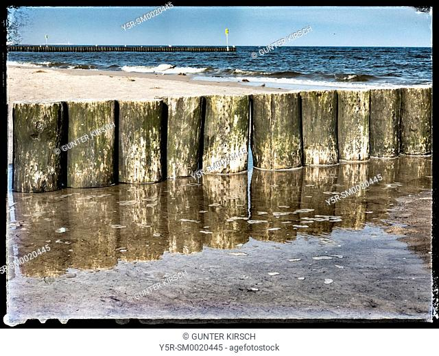 Groynes at the beach of the Baltic Sea in Kolobrzeg. Groynes are intended to break the shaft and to prevent the erosion of the coast, Kolobrzeg, West Pomeranian
