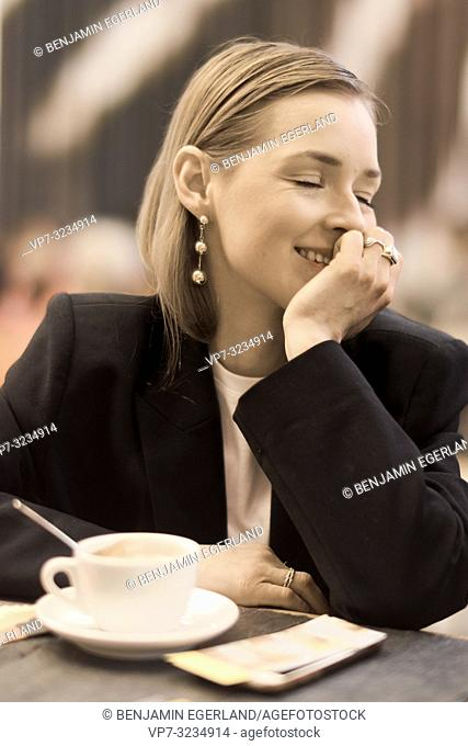 fashionable blogger woman with coffee cup, taking a break in café, happy smiling, closed eyes, in Munich, Germany