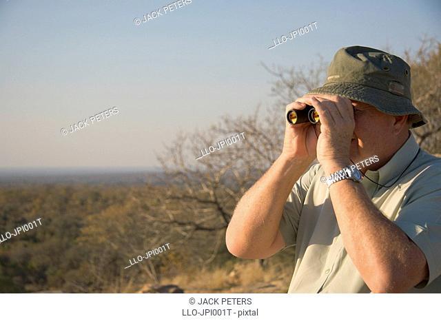 Senior man looking through binoculars. Kruger National Park, Mpumalanga Province, South Africa
