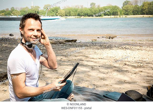Portrait of smiling man sitting on blanket at a river using tablet