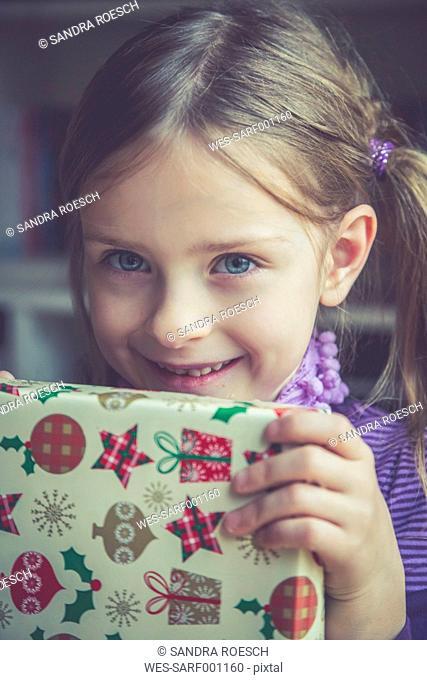Portrait of smiling little girl holding Christmas present
