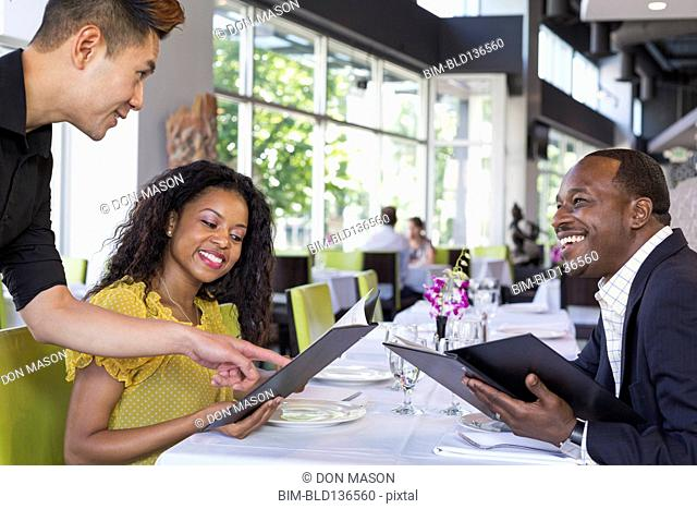 Waiter explaining menu to couple in restaurant