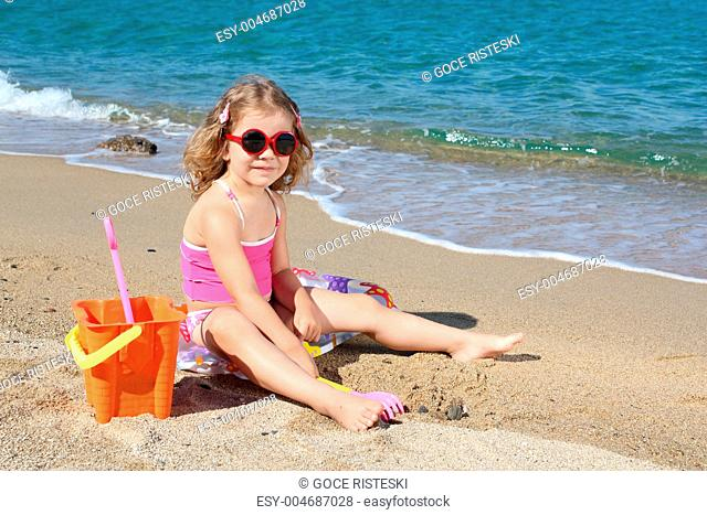 little girl with sunglasses playing on beach