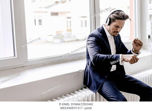 Passionate businessman listening to music on headphones