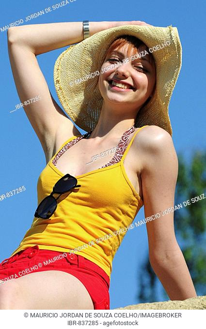 Red-haired woman wearing a yellow top, sun hat, sitting on a rock, summer, attractive, smiling
