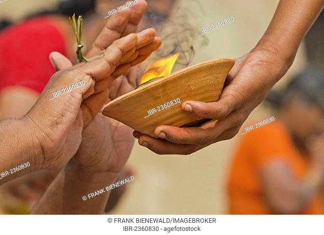 Hands over fire as part of the ritual to pray farewell for the soul of a deceased person, at the ghats of Varanasi, India, Asia