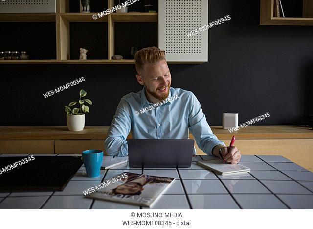 Smiling businessman with laptop and notebook working at home