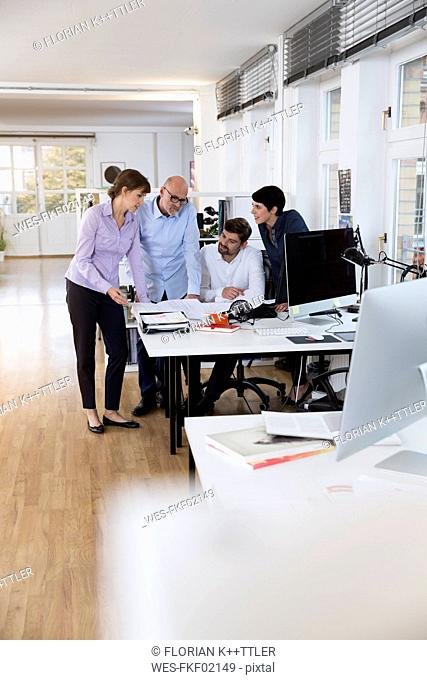 Colleagues working together at desk in office