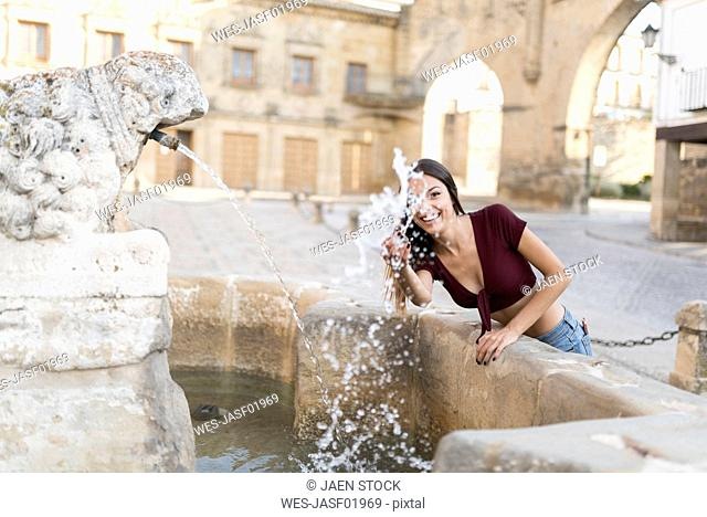 Spain, Baeza, smiling young woman splashing with water of a fountain