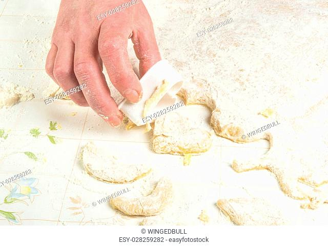 making homemade sugar cookies - woman's hands, form a dough and the flour on the table