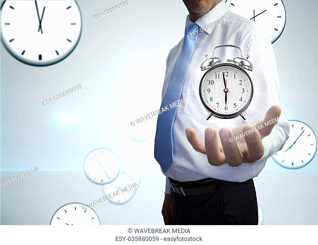 Business man holding a clock against background with clocks