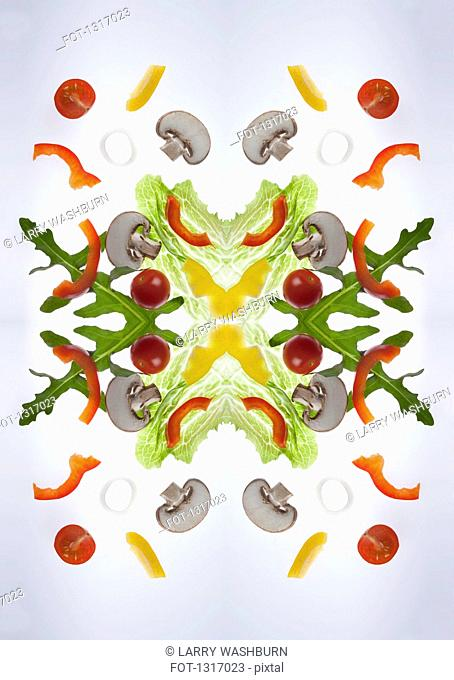 A digital composite of mirrored images of pieces of a mixed vegetable salad