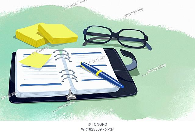 a pair of glasses next to a notebook