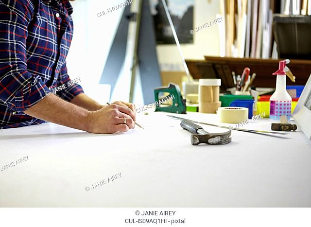 Mid adult man writing measurement on workbench in picture framers workshop