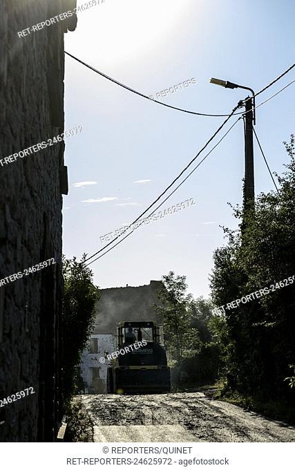 Upgrading and asphalting the streets of a village. Bitumen surfacing and compaction. Entretien et asphaltage avec tremie, repandeuse