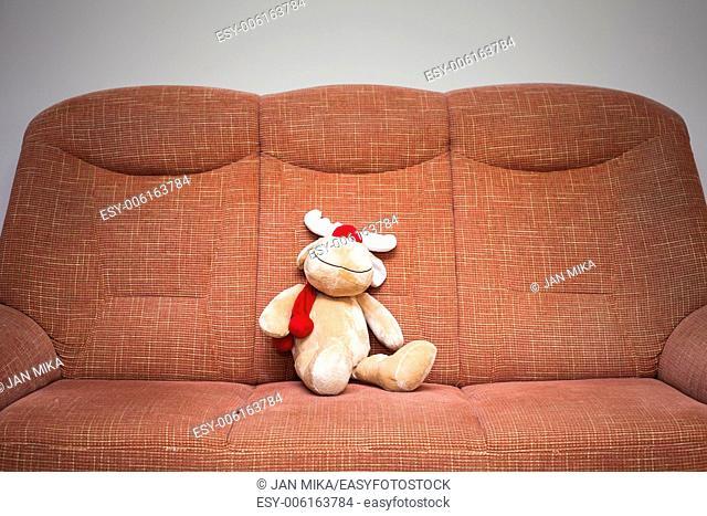 Christmas reindeer stuffed toy sitting on sofa