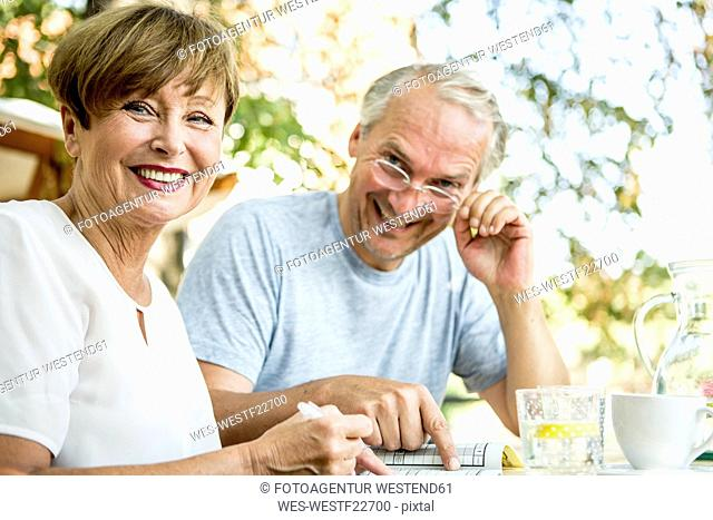Smiling senior couple outdoors doing crossword puzzle together